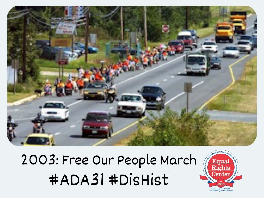 Polaroid-style photograph of participants in the Free Our People March walking and rolling down the side lane of a busy street. Captioned, 2003: Free Our People March #ADA31 #DisHist