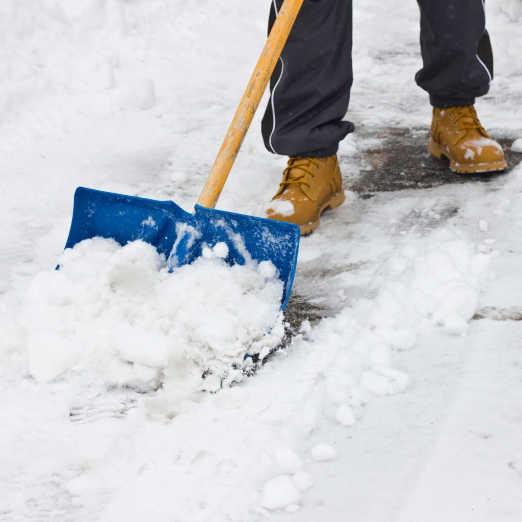 (photo) a person shovels snow off of the sidewalk.