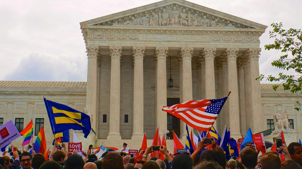 A crowd in front of the Supreme Court holds up LGBT pride and marriage equality flags