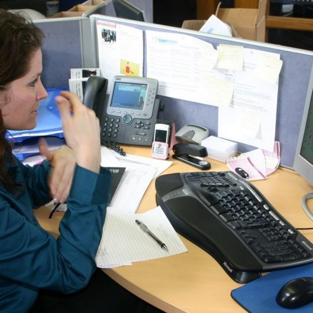 Photograph of a Deaf woman using a Video Relay Service to communicate with a hearing person.